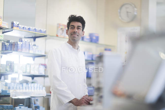 Welcoming pharmacist standing at counter in drugstore interior — Stock Photo