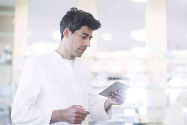Farmacista metà adulto con il medicamento utilizzando la tavoletta digitale in farmacia — Foto stock