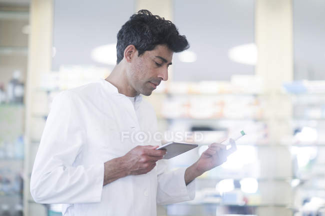 Mid adult pharmacist with medicament using digital tablet in pharmacy — Stock Photo