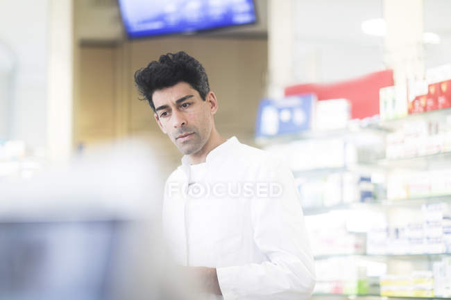 Mid adult pharmacist working in drugstore interior — Stock Photo