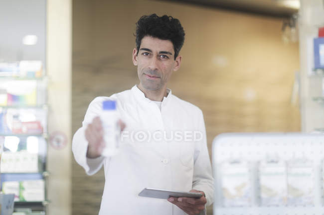 Male druggist with digital tablet offering medicament in pharmacy interior — Stock Photo