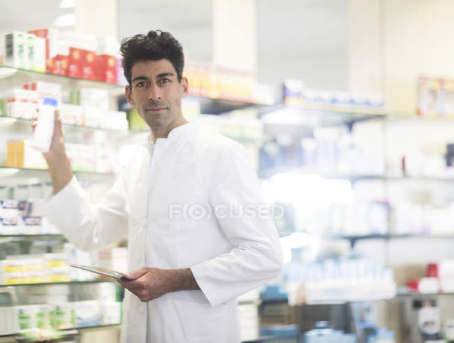 Mid adult pharmacist holding medicament and digital tablet in drugstore — Stock Photo