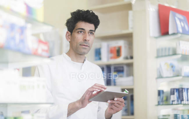 Mid adult pharmacist using digital tablet in drugstore interior — Stock Photo