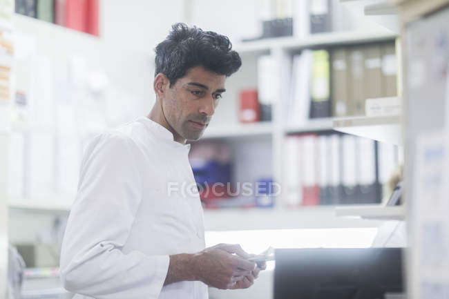 Mid adult pharmacist working with digital tablet in drugstore — Stock Photo
