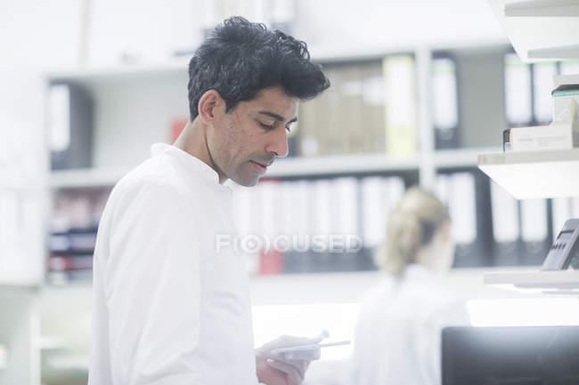 Farmacista di adulto metà lavoro con tavoletta digitale in farmacia — Foto stock
