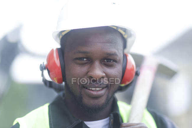 Construction worker in protective headphones holding hammer and looking in camera — Stock Photo