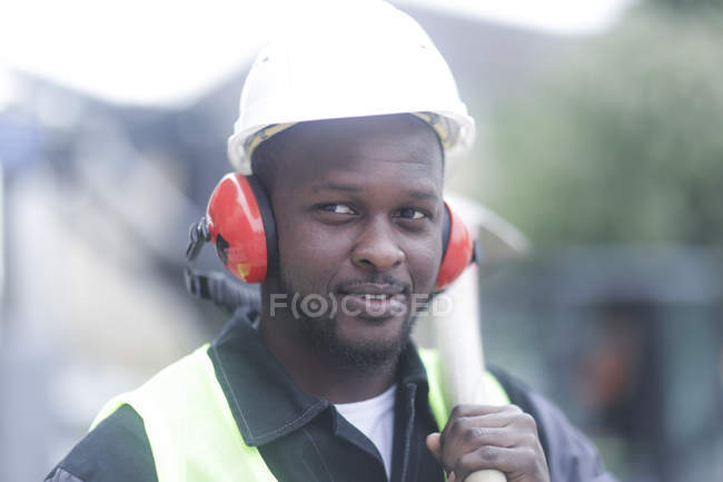 Construction worker in protective headphones holding hammer and looking away — Stock Photo