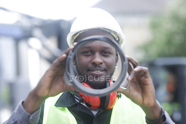 Construction worker holding round machinery detail and looking in camera — Stock Photo