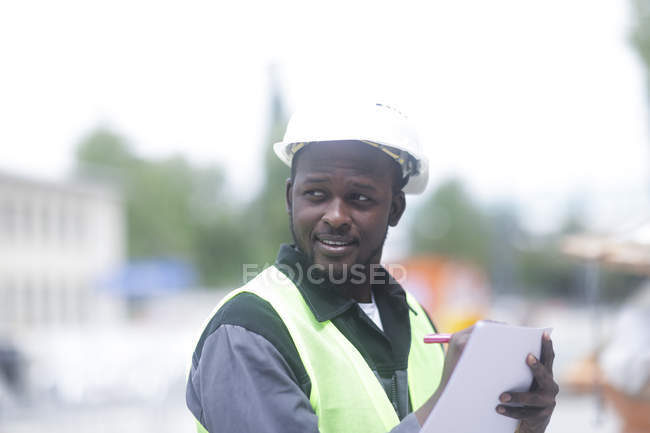African American engineer making notes on blueprint and looking away — Stock Photo