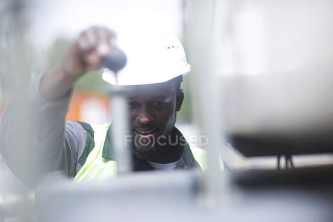 Construction worker adjusting equipment on building site — Stock Photo