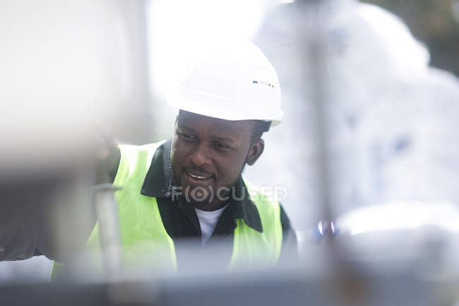 Construction worker using digital tablet for adjusting equipment — Stock Photo
