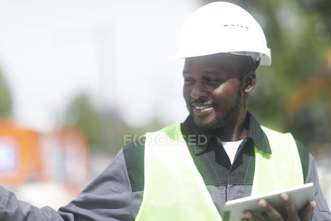 African American engineer holding digital tablet and looking away — Stock Photo