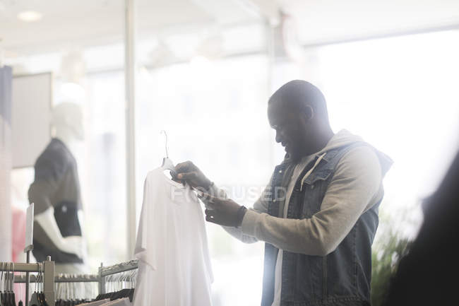 Mid adult man selecting t-shirts in clothes store — Stock Photo