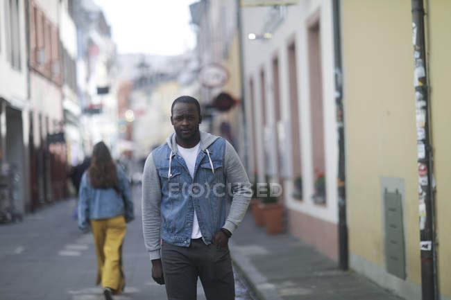 Zuversichtlich Mitte erwachsener Mann in Jeans Jacke stehen auf der Straße in der Stadt — Stockfoto