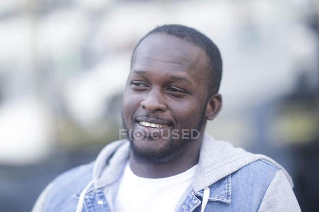 Retrato de homem afro-americano, sorrindo e olhando para fora na rua — Fotografia de Stock