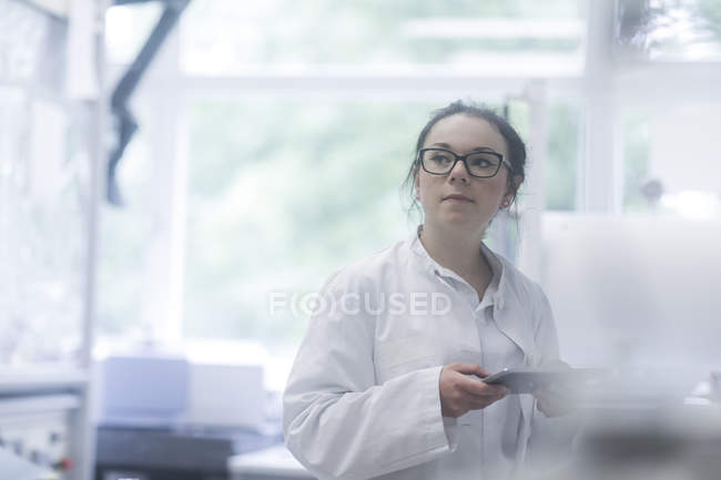 Female lab assistant using digital tablet in biological laboratory. — Stock Photo