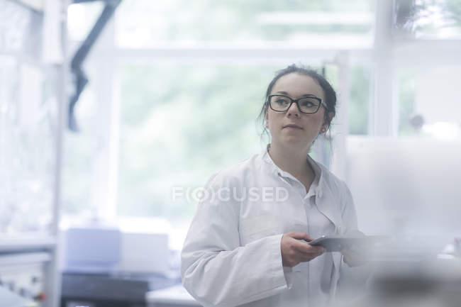 Weibliche Laborantin mit digital-Tablette im biologischen Labor — Stockfoto