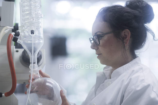 Female technician adjusting chemical apparatus in laboratory. — Stock Photo