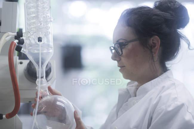 Female technician adjusting chemical apparatus in laboratory. — Stock Photo