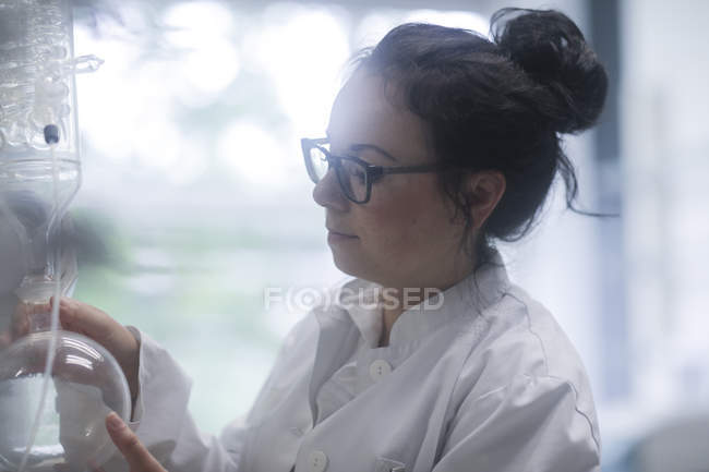 Female scientist adjusting chemical apparatus in laboratory. — Stock Photo