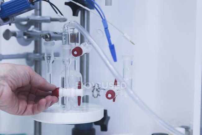 Close-up of female scientist hand adjusting chemical apparatus in laboratory. — Stock Photo