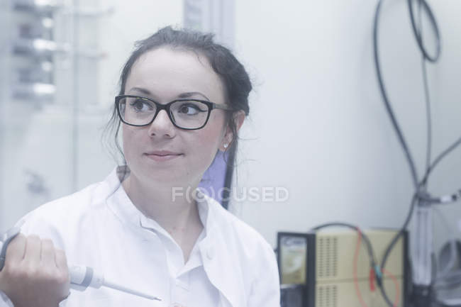 Female chemist using pipette and looking away in laboratory. — Stock Photo