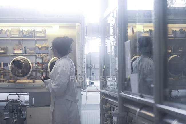 Female scientist standing in biological laboratory and looking at equipment. — Stock Photo