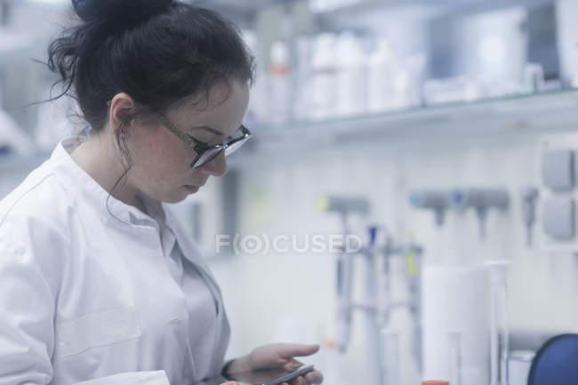 Female scientist using digital tablet in biological laboratory. — Stock Photo