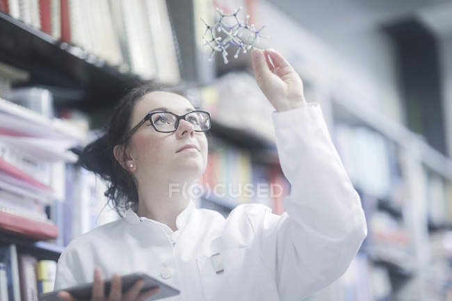 Female chemist with digital tablet examining molecular model in laboratory. — Stock Photo