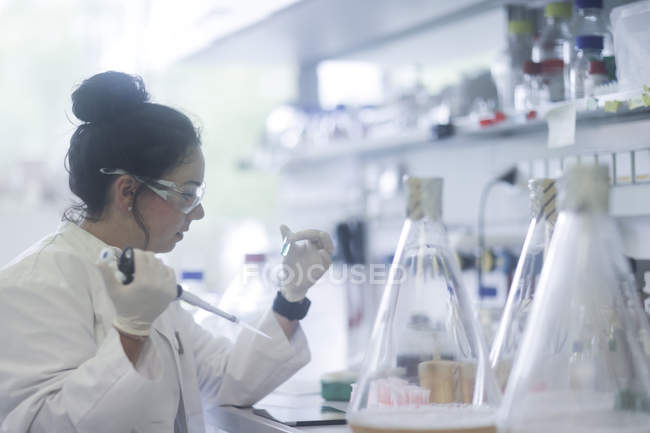 Young biologist pipetting liquid into microtube in laboratory. — Stock Photo