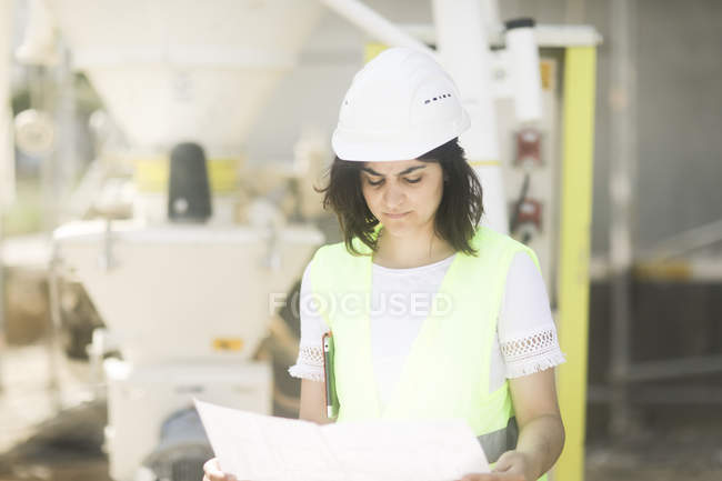 Front view of female building surveyor standing at construction site — Stock Photo