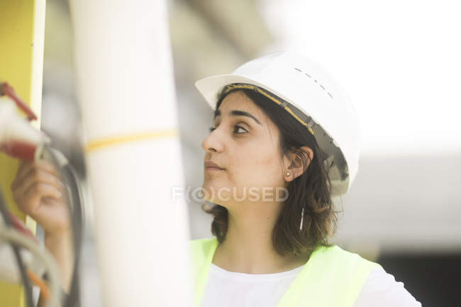 Portrait of female building surveyor examining industrial equipment — Stock Photo
