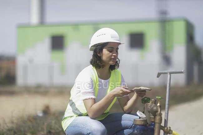 Female building surveyor examining industrial equipment — Stock Photo