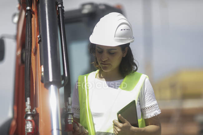 Young adult female building surveyor examining industrial equipment — Stock Photo