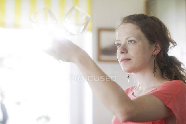 Mid adult woman holding and examining wine glasses at home. — Stock Photo