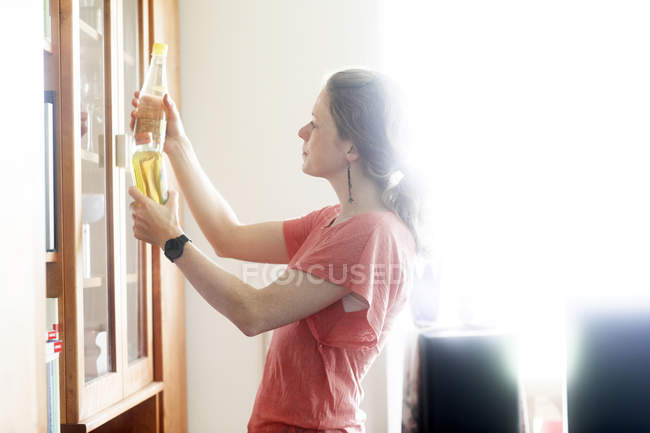 Side view of woman examining yellow liquid in bottles in home interior. — Stock Photo