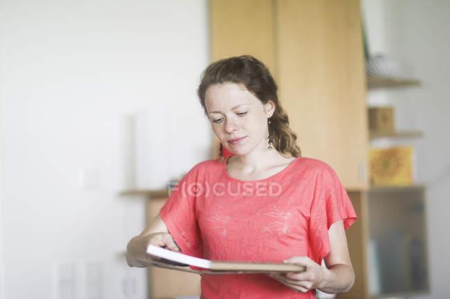 Femme dans les documents de prise de t-shirt rose de paquet à l'intérieur de la maison — Photo de stock