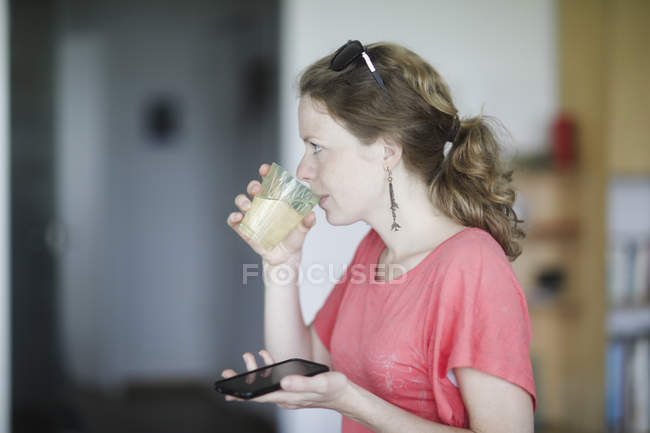 Side view of woman drinking water and holding smartphone in home interior. — Stock Photo