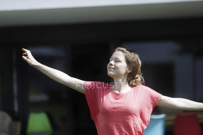Mid adult woman in pink t-shirt stretching in street. — Stock Photo