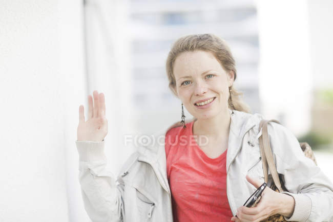 Portrait of mid adult woman with smartphone waving and looking in camera town. — Stock Photo
