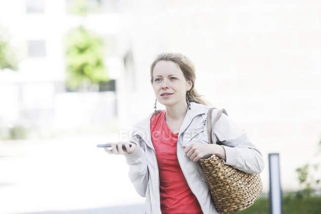 Женщина с хвост в куртке, держа плечо сумку и мобильный телефон на улице — стоковое фото
