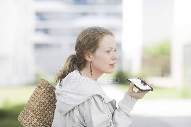 Woman in jacket holding wicker handbag and using smartphone in street. — Stock Photo