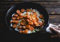 Mãos segurando a frigideira com vegetais crus — Fotografia de Stock