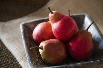 Pere rosse in ciotola di ceramica rustica — Foto stock