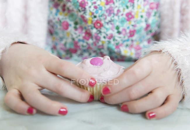 Kleine Mädchen halten cupcake — Stockfoto