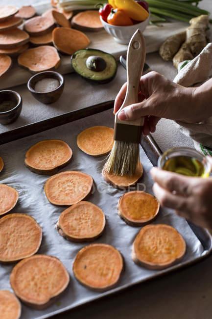 Женщина, охватывающих картофель с оливковым маслом — стоковое фото