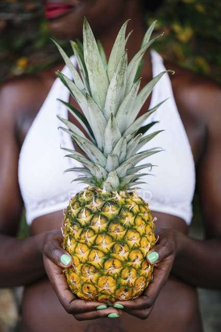 Woman holding fresh pineapple — Stock Photo