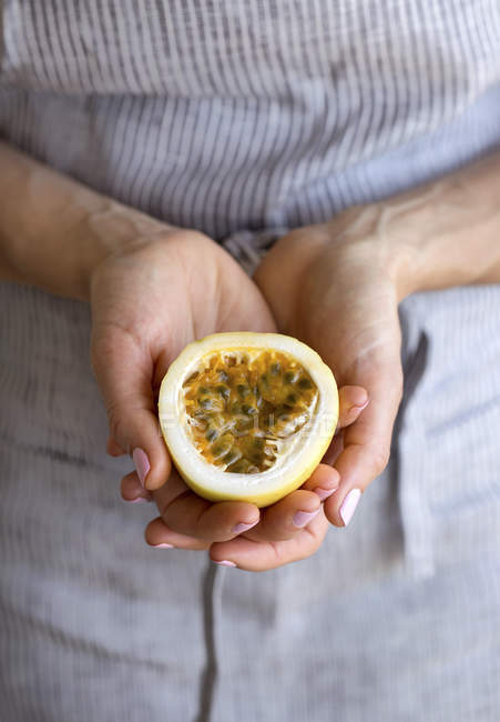 Female hands holding passion fruit — Stock Photo