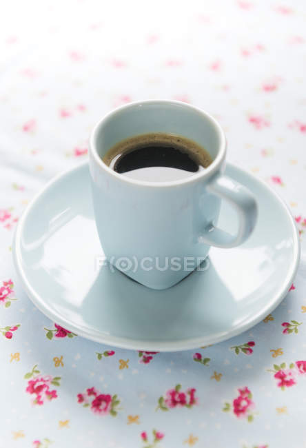 Caffè espresso su tovaglia floreale — Foto stock