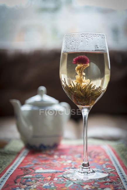 Boire du thé avec fleur en verre — Photo de stock